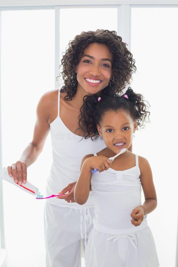 有她的刷他们的牙的女儿的俏丽的母亲 库存图片