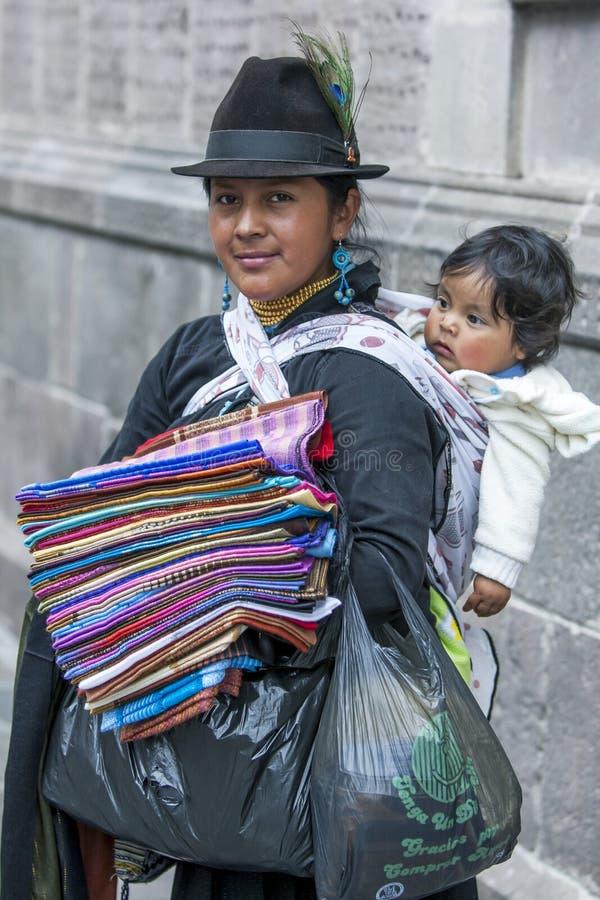 有她的卖纺织品的孩子的一个夫人在独立广场在基多在厄瓜多尔在南美 免版税库存照片