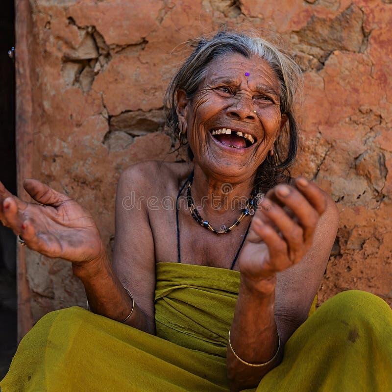 有她的后面agaist的笑的老尼泊尔妇女土制墙壁 图库摄影