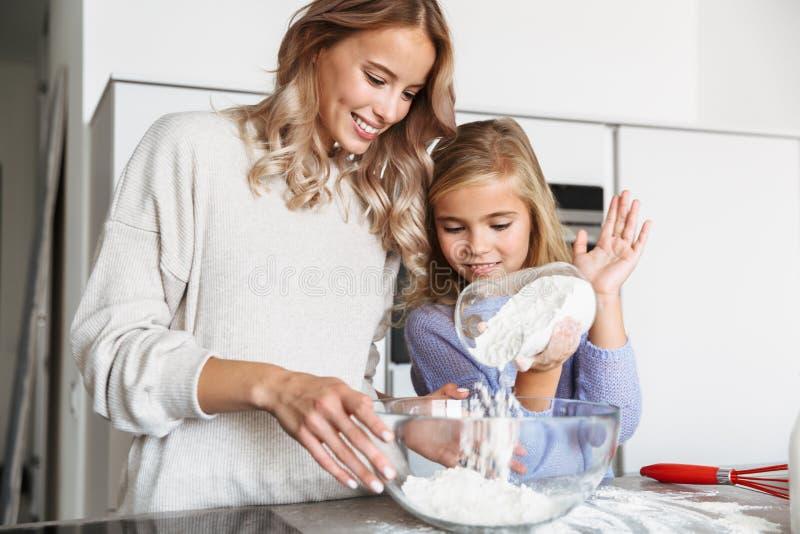 有她的在家户内妹厨房的妇女烹调用面粉的 免版税库存图片