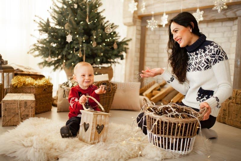有她的坐和使用以圣诞树为背景的儿子的母亲 库存图片