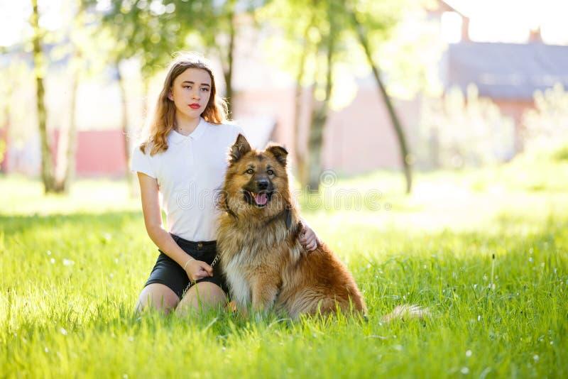 有她的坐在公园的狗的少年微笑的女孩 免版税库存照片