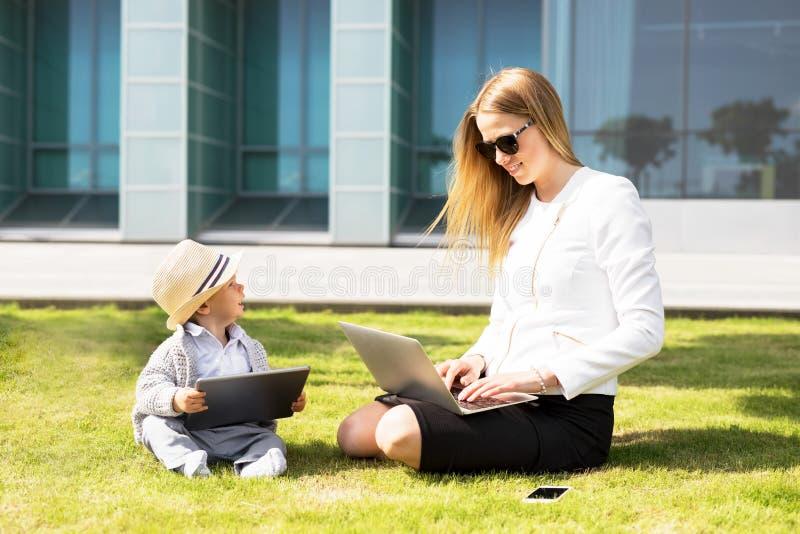 有她的坐在草和工作在便携式的信息装置的孩子的妇女 图库摄影