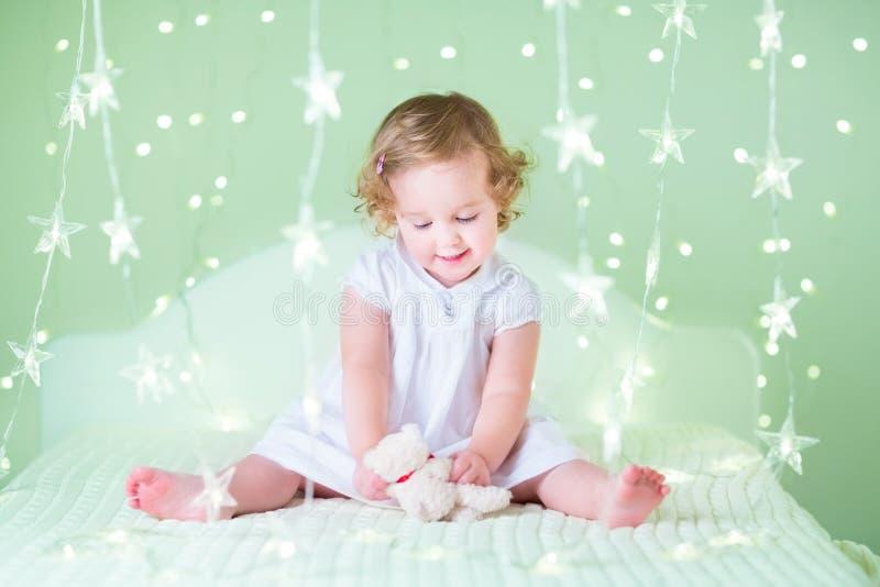 有她的坐在绿色圣诞灯之间的熊玩具的甜小孩女孩 库存图片