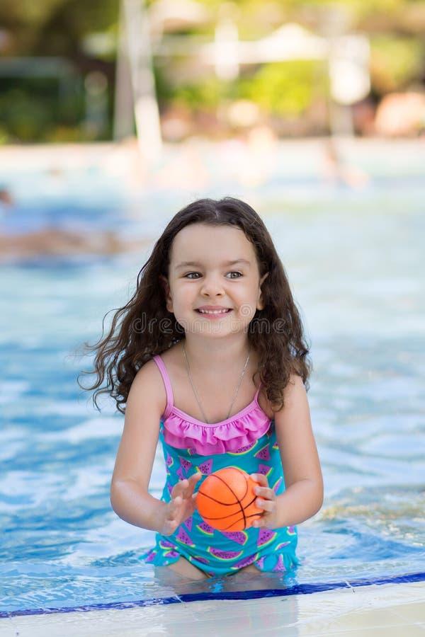 有她的头发的愉快的女孩下来在打在水池的明亮的泳装球在一个晴朗的夏日 免版税图库摄影