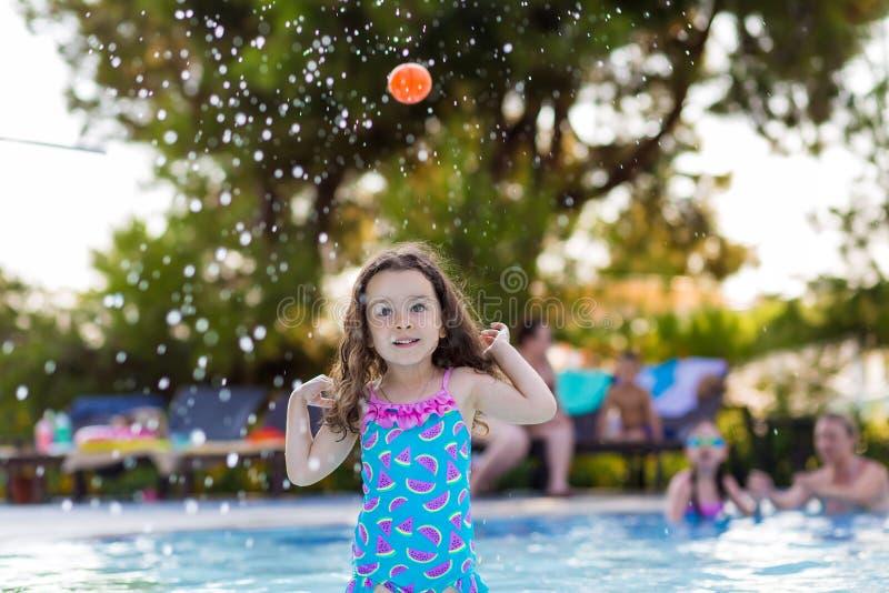 有她的头发的愉快的女孩下来在打在水池的明亮的泳装球在一个晴朗的夏日 免版税库存图片