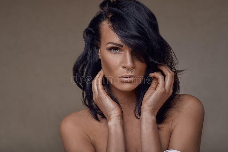 有她的头发的美丽的中年深色的妇女清扫了一只眼睛 免版税库存照片