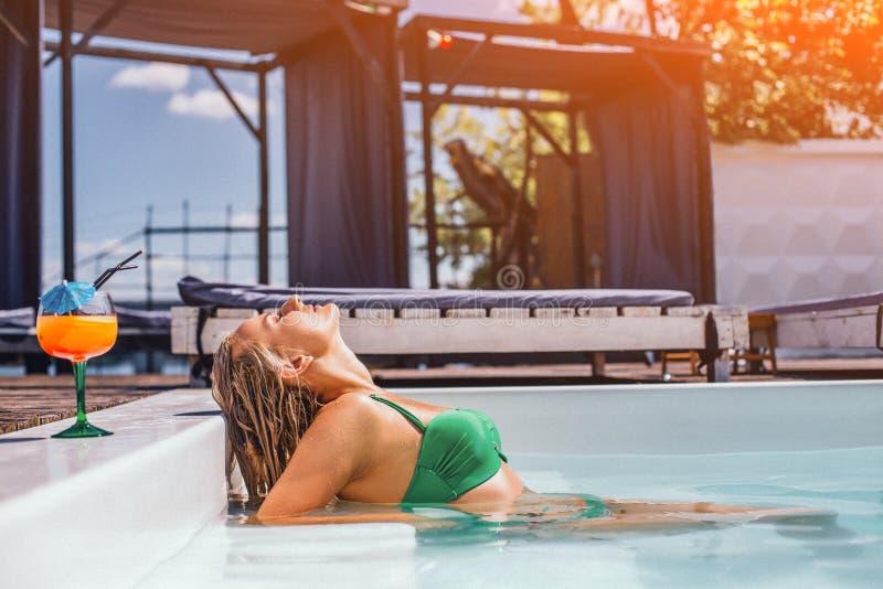 有她的头的金发碧眼的女人晒日光浴在游泳场 库存图片