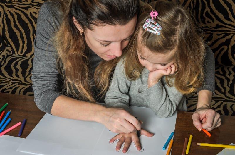 有她的女儿凹道的年轻美丽的母亲与在纸的五颜六色的铅笔,愉快的家庭 库存图片