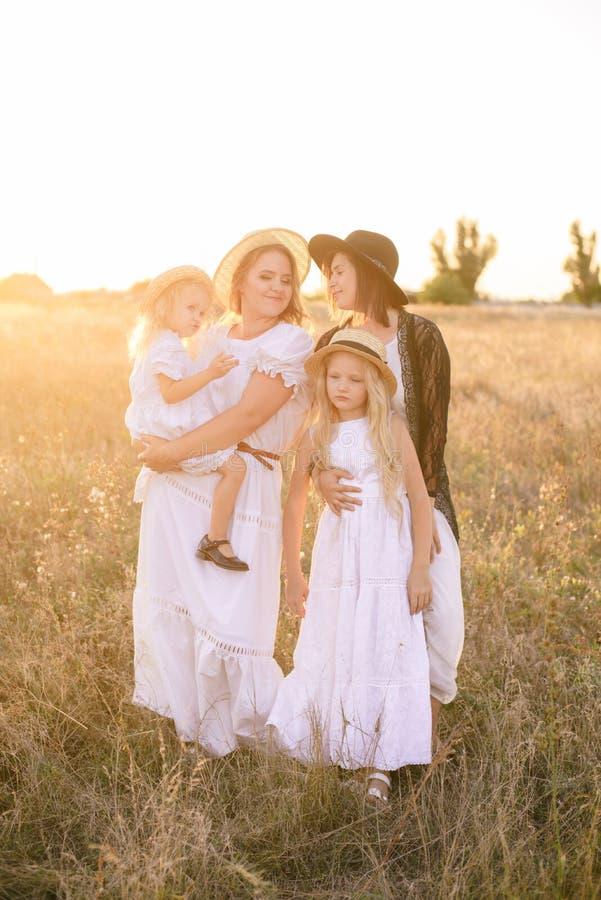 有她的女儿和一个伯母的一个年轻母亲有在白色礼服的金发的在日落在乡下的领域的夏天 免版税库存图片