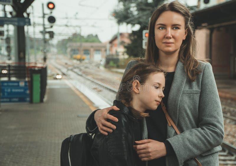 有她的女儿的妇女火车站的 库存图片