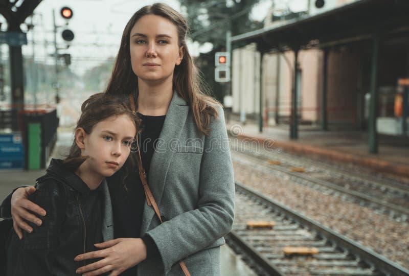 有她的女儿的妇女火车站的 图库摄影
