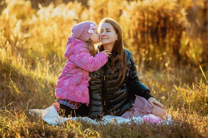 有她的女儿的年轻美丽的母亲步行的在一晴朗的秋天天 他们坐在草,女儿kisse的格子花呢披肩 免版税图库摄影
