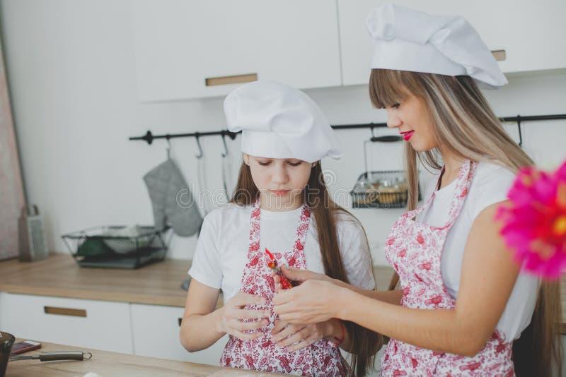 有她的女儿的母亲准备小圆面包 库存照片