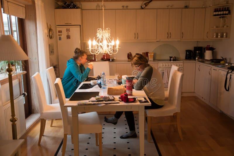 有她的女儿的母亲吃在晚餐在厨房里 免版税库存照片