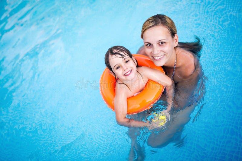 有她的女儿的美丽的妇女游泳池的 库存图片