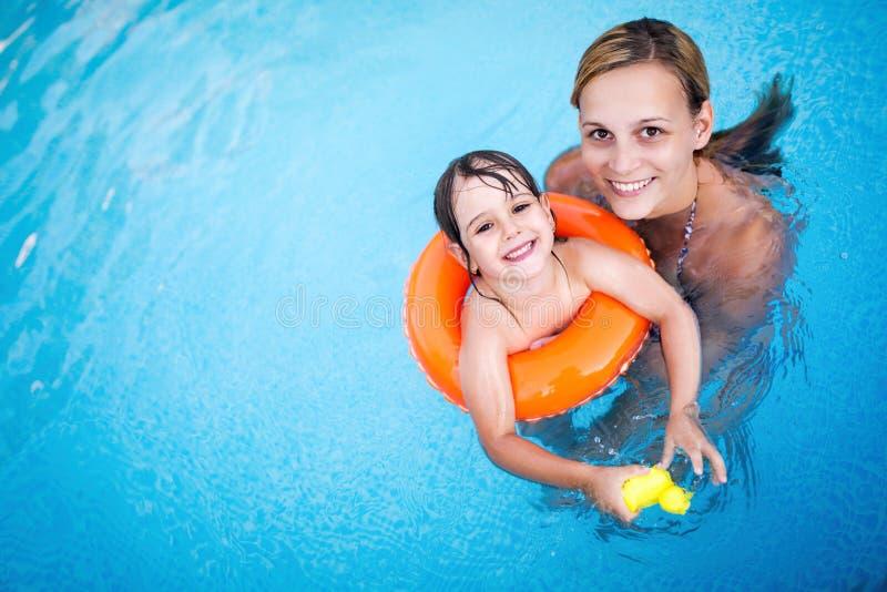 有她的女儿的美丽的妇女游泳池的 库存照片