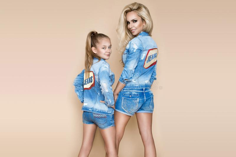 有她的女儿的美丽的白肤金发的妇女牛仔布夹克和短裤的 在牛仔裤衣物的时装模特儿 免版税库存照片