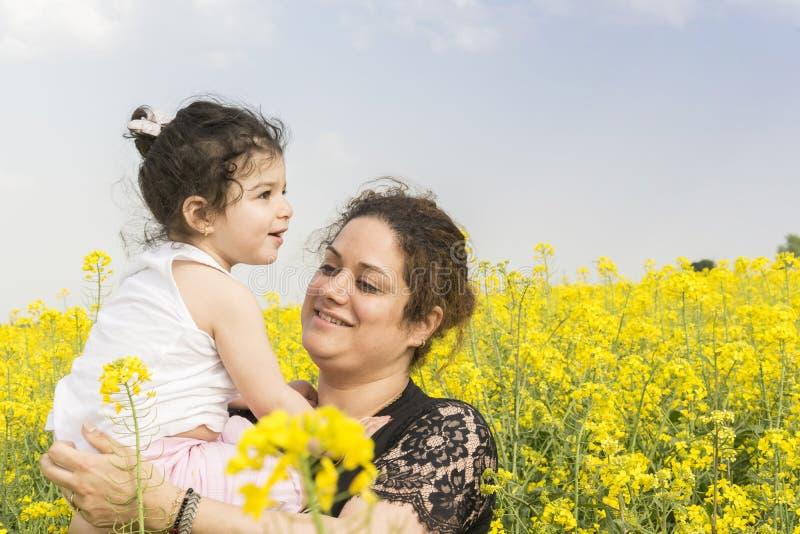 有她的女孩的年轻母亲油菜领域家庭的在油菜农场一起享用 免版税图库摄影