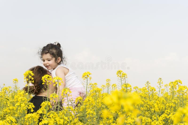 有她的女孩的母亲获得乐趣在油菜领域家庭统一性概念 免版税库存图片