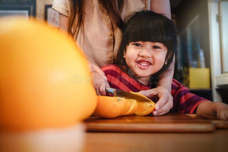 有她的妈妈切片的愉快的逗人喜爱的3-4岁女孩在木表上的某一桔子在餐具室屋子里 少女学会有她的厨师 库存照片