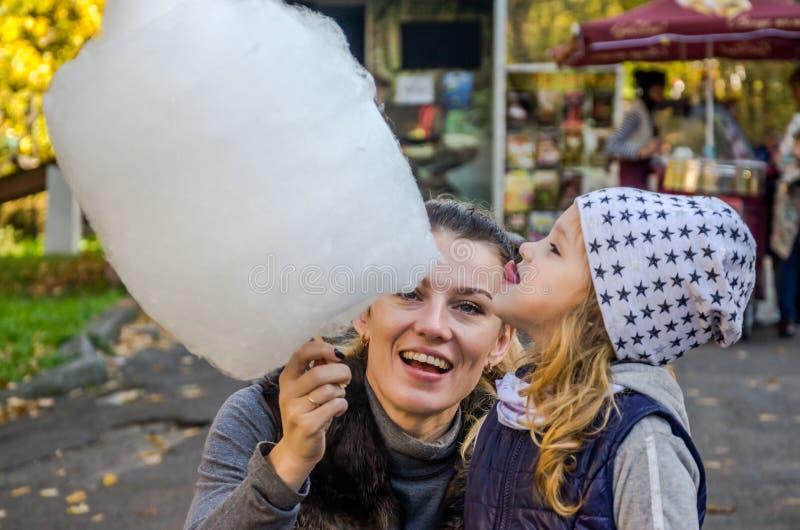 有她的妈妈的一个小迷人的女孩在游乐园-一个愉快的家庭吃着巨大的棉花糖 库存照片