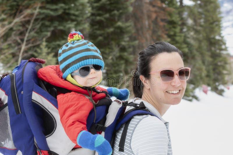 有她的婴孩的年轻妈妈Snowshoeing背包的 图库摄影