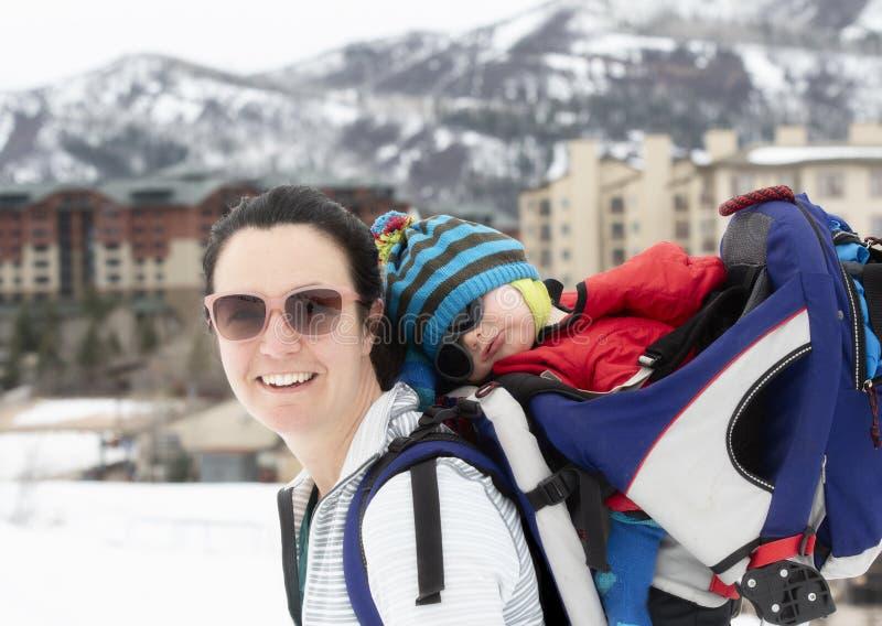 有她的婴孩的年轻妈妈Snowshoeing背包的 库存照片