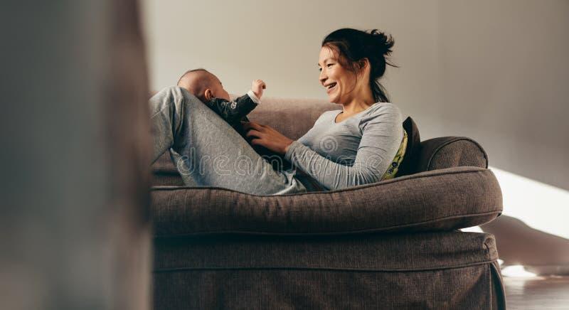 有她的婴孩的母亲坐长沙发 库存图片