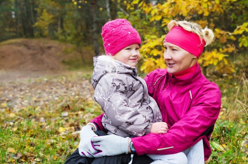 有她的孙女的祖母在秋天公园 库存照片