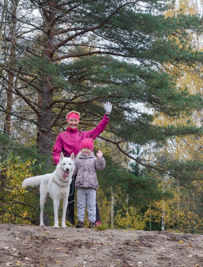 有她的孙女的老婆婆和狗在公园走 免版税图库摄影