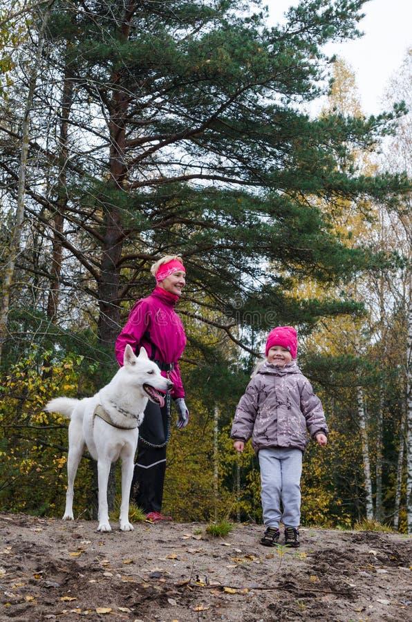 有她的孙女的老婆婆和狗在公园走 免版税库存图片