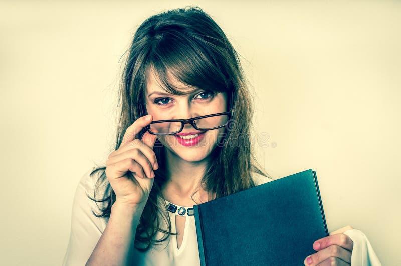 有她的学术论文工作的愉快的毕业生妇女在白色 免版税库存照片