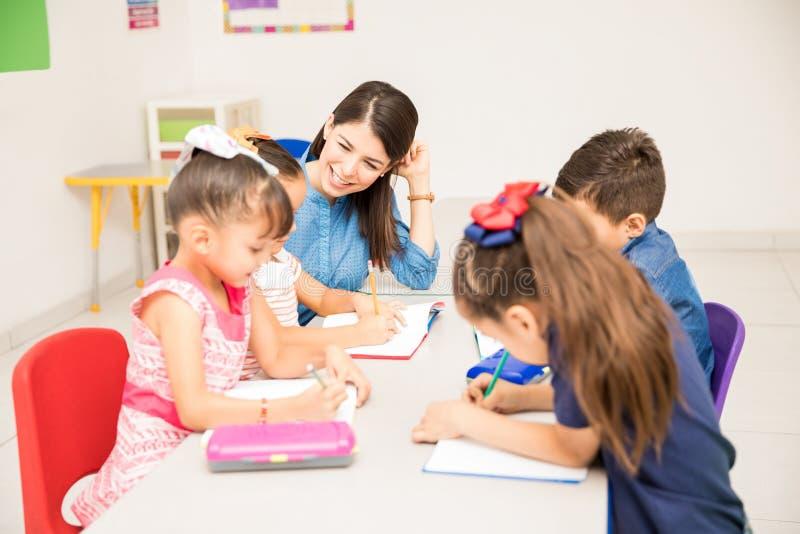 有她的学生的幼儿园老师 免版税图库摄影