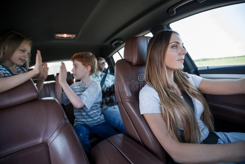 有她的孩子的妈妈在家用汽车 免版税库存照片