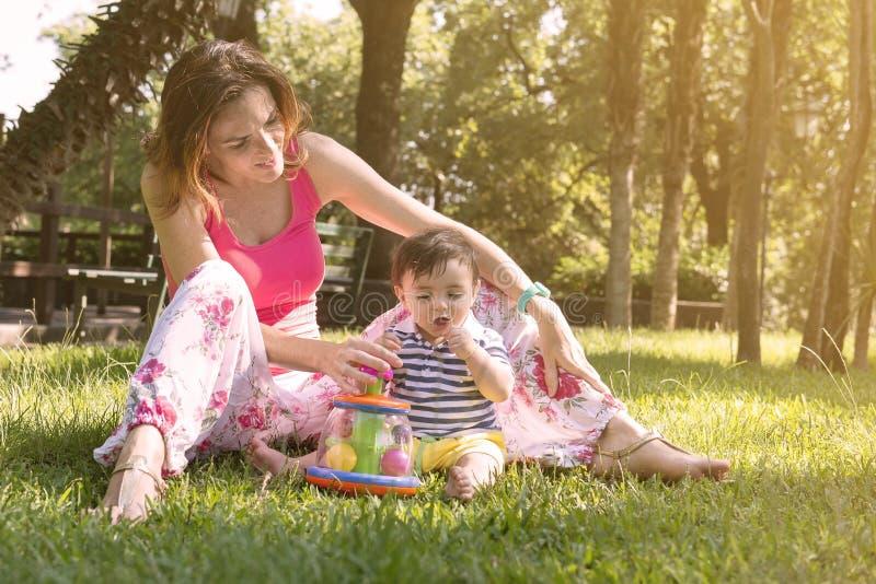 有她的孩子的母亲公园温暖的过滤器的申请了 库存照片
