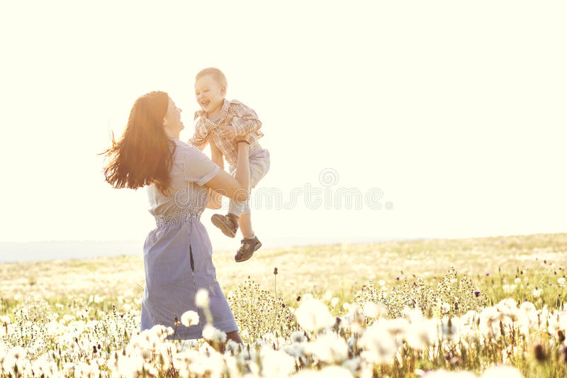 有她的孩子的母亲在阳光下 免版税图库摄影