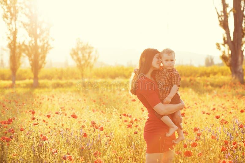 有她的孩子的母亲在阳光下 库存图片