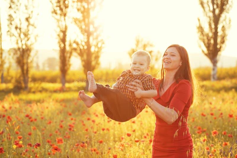 有她的孩子的母亲在阳光下 库存照片