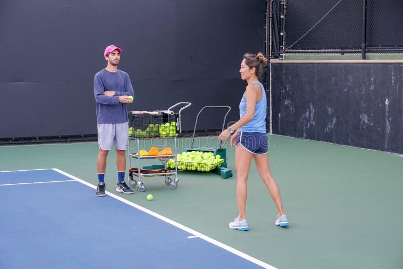 有她的实践室外网球的教练员的亚裔年轻女人 免版税库存图片