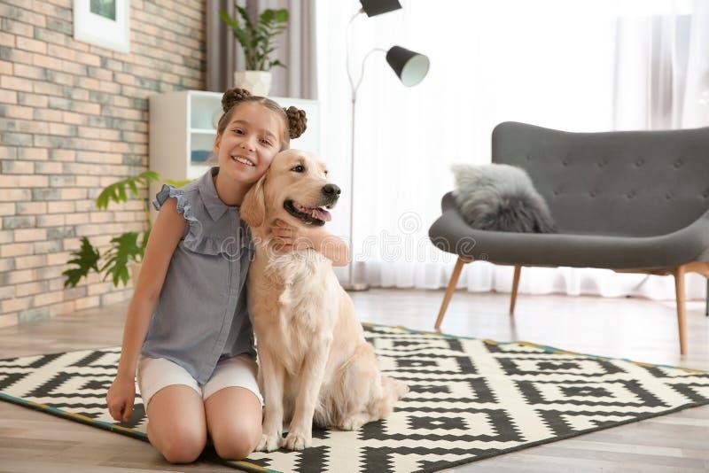 有她的宠物的逗人喜爱的小孩在地板上 库存照片