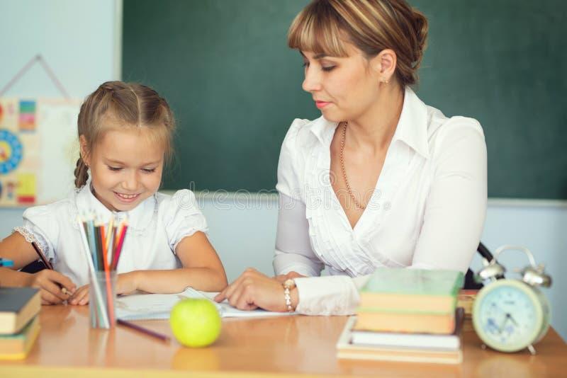 有她的家庭作业的老师帮助的女小学生在教室在学校 免版税库存照片