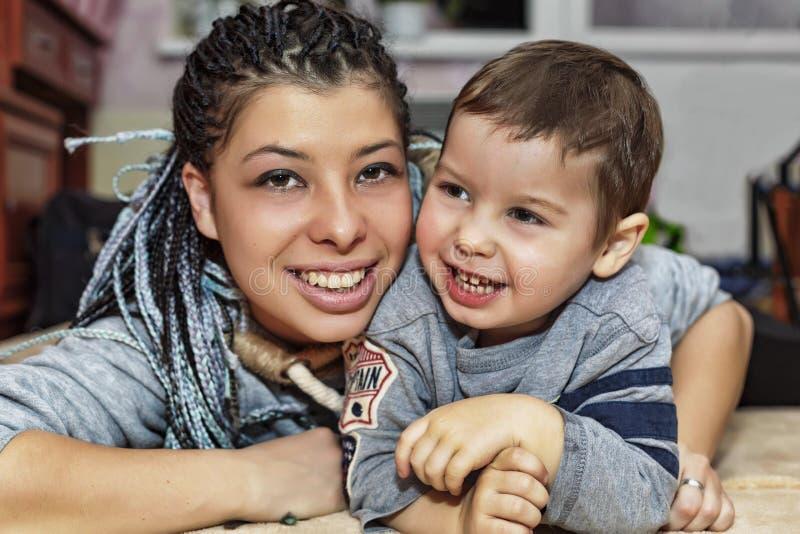 有她的小儿子的一个愉快的深色皮肤的母亲使用并且笑 库存照片
