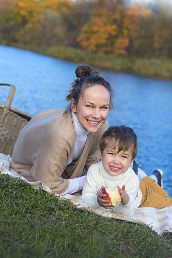 有她的小儿子的年轻俏丽的母亲在秋天公园 库存照片