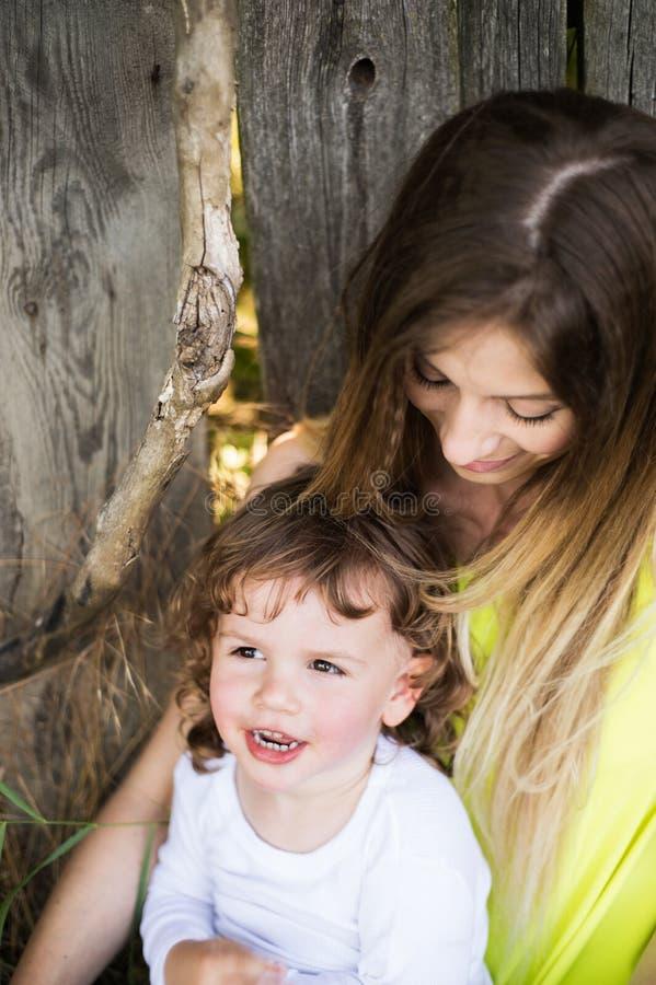 有她的小儿子的美丽的母亲反对老木篱芭 免版税图库摄影