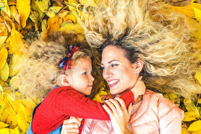 有她的小女儿的母亲获得乐趣在公园 免版税库存照片