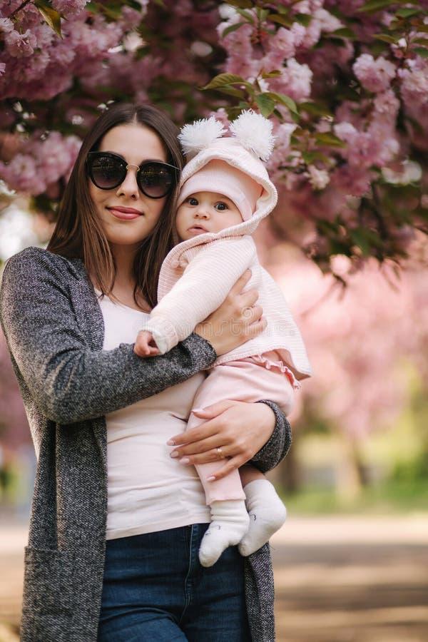 有她的小女婴的美丽的妈妈 太阳镜的妈妈 r 库存照片