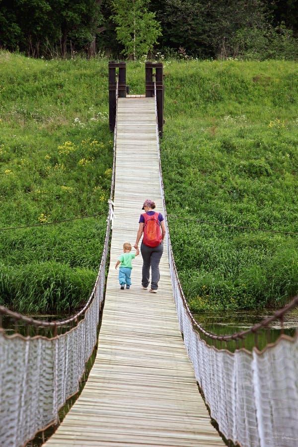有她的小孩儿子步行的母亲在吊桥 冒险家 免版税图库摄影
