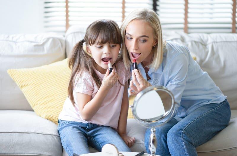 有她的小逗人喜爱的女儿的美丽的妈妈做着您的构成并且获得乐趣 妈妈和女儿佩带唇膏神色在镜子 免版税库存图片