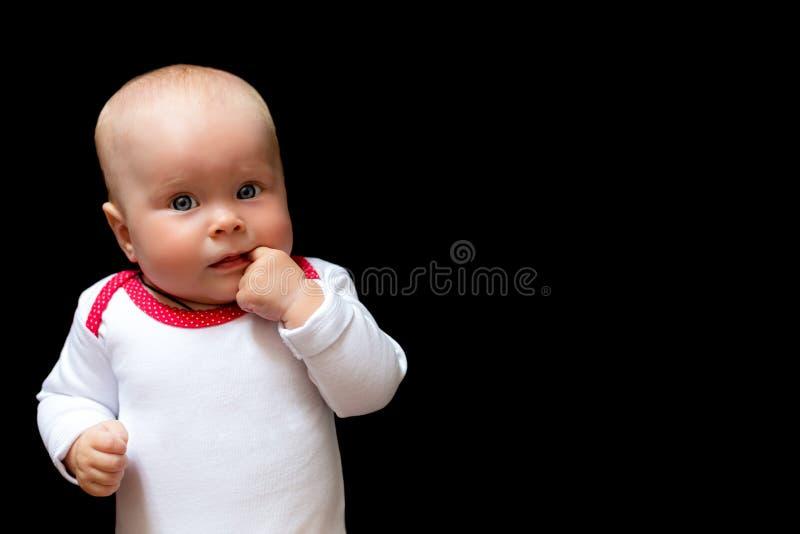 有她的手指的可爱和逗人喜爱的女婴在嘴 黑背景的婴儿和文本的空间 库存图片